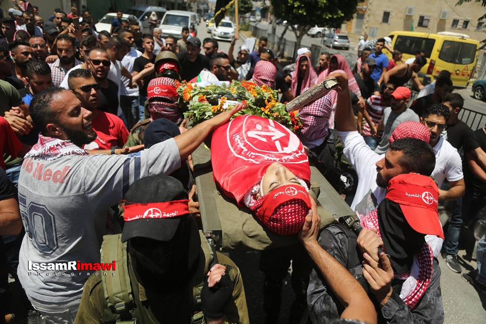 The funeral held for Arkan Thayeir Muzhir in the Dheishe refugee camp. His body is wrapped for burial in a PFLP flag and carried on the shoulders of masked PFLP operatives (QudsN Facebook page, July 23, 2018).