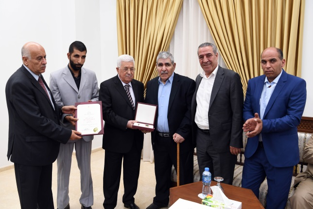 Mahmoud Abbas awards certificates and plaques to the families of prisoners (Wafa, July 23, 2018).