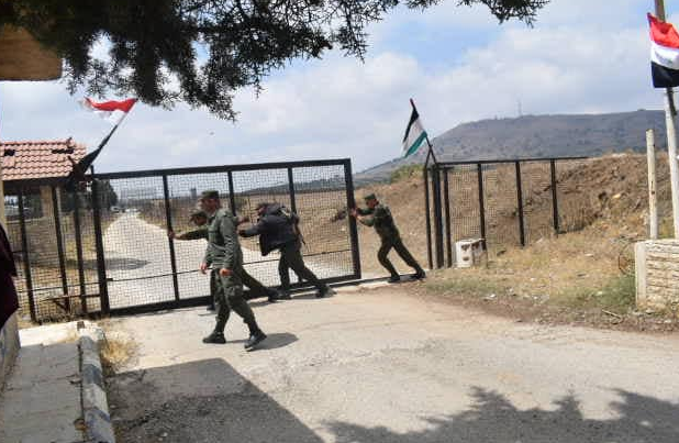 Syrian army soldiers opening the Quneitra crossing, with the Syrian flag waved above.