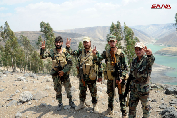 Syrian army soldiers making the victory sign with the Yarmouk Basin in the background.