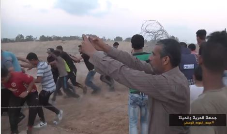 ‏‏Rioters drag barbed wire away from the security fence in the central Gaza Strip (from a video from the Facebook page of the Supreme National Authority of the Return March, August 10, 2018).