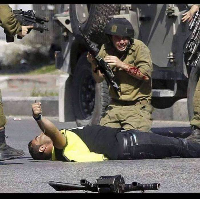 A wounded IDF soldier. The terrorist is still holding the knife he used to stab him (Khabar News Agency, October 16, 2018).