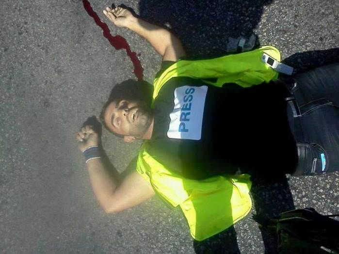 Terrorist Iyad al-'Awauda, killed during a stabbing attack on an IDF soldier in the Hebron region. He was wearing a yellow vest and a Press T-shirt.
