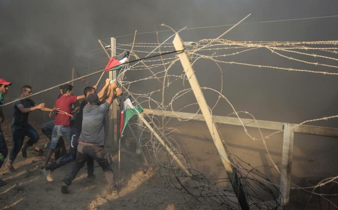 Gazan rioters try to break through the security fence during a