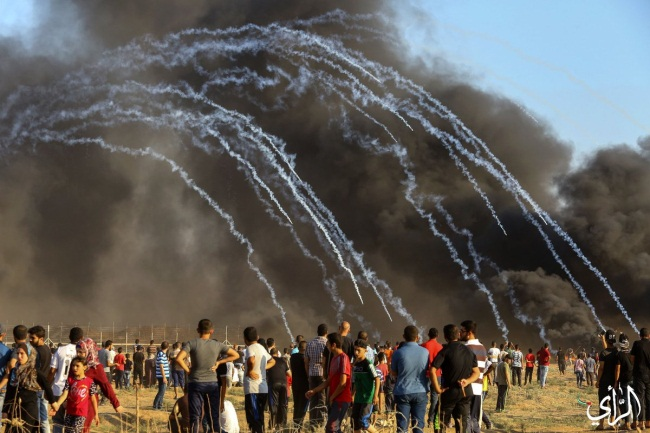 Gazans burn tires near the security fence.