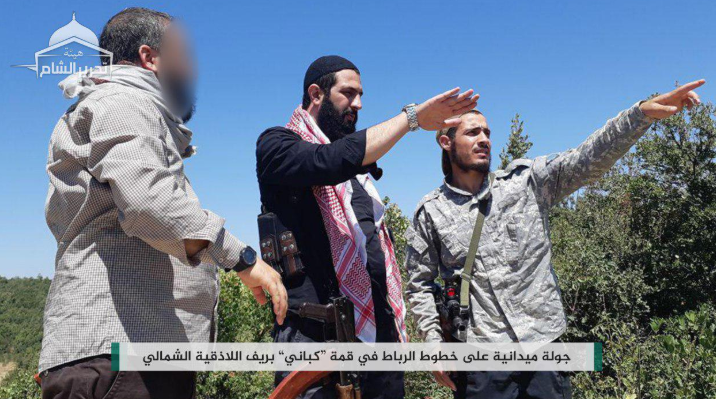 Abu Mohammad Al-Julani (center, in black), commander of the Headquarters for the Liberation of Al-Sham, during a visit to the organization's defense lines at the summit of the Kabani Mountain, the Kurds' Mountain (northeast of Latakia).
