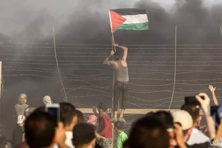 A Gazan hangs a Palestinian flag on the security fence east of Gaza City.
