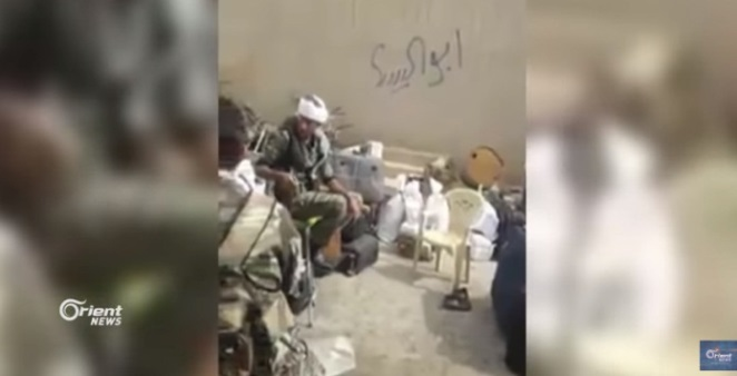 Fighters of the National Defense Forces with property looted from residents' homes in the city of Albukamal (Orient News YouTube channel, August 19, 2018)