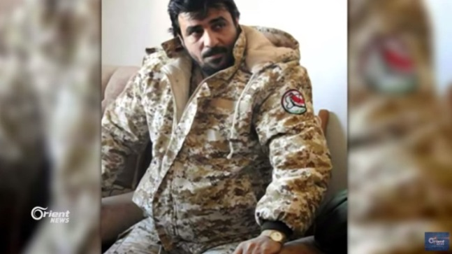 Local commander of the National Defense Forces, codenamed Firas al-Iraqi, detained by the Shiite militias in Albukamal (Orient News YouTube channel, August 19, 2018). The insignia of the National Defense Forces can be seen on his sleeve (right).