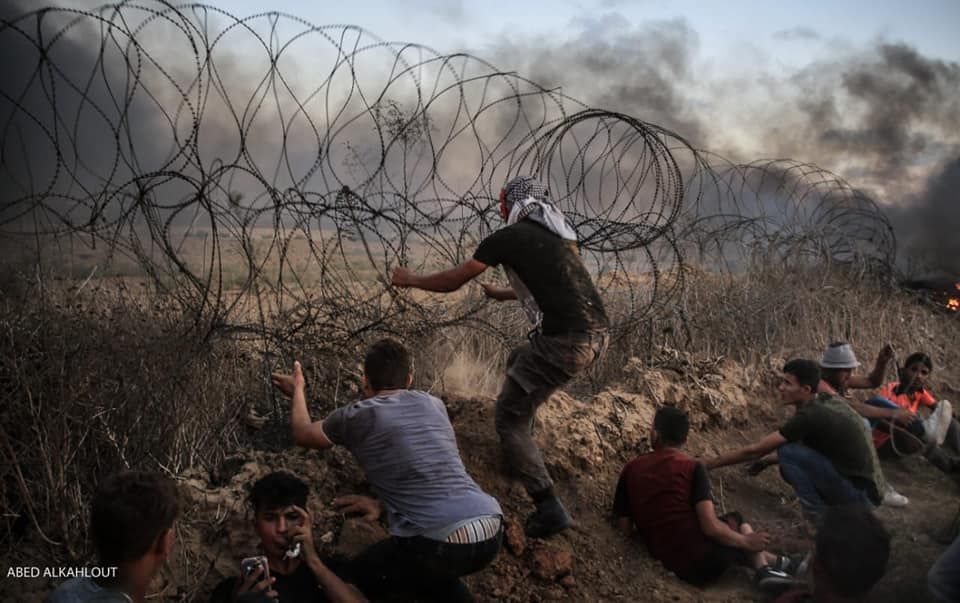 "Clashes during the ""return march"" in eastern Gaza City. Breaking through the security fence, and a Palestinian holding a Molotov cocktail (Facebook page of the Supreme National Authority of the Return March, September 14, 2018)"