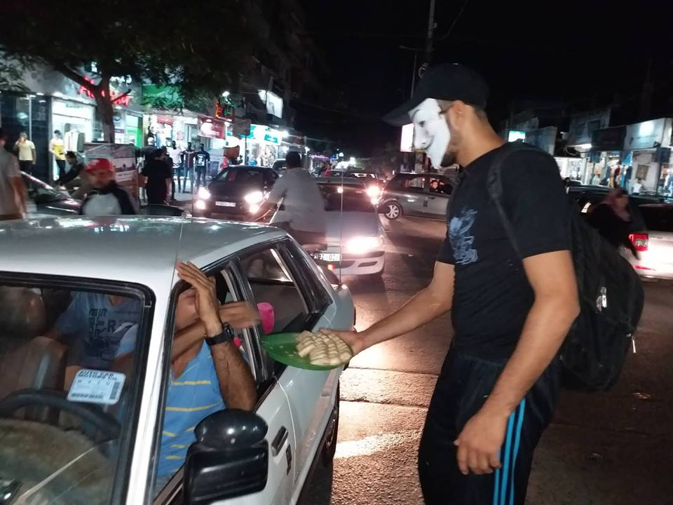 Masked Gazan hands out cookies after the attack (QudsN Twitter account, October 7, 2018). Palestinian Tweets after the attack.