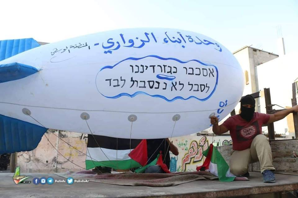 The Sons of al-Zouari balloon group launches a giant balloon from the central Gaza Strip, threatening the Israeli communities near the border. The Hebrew reads,