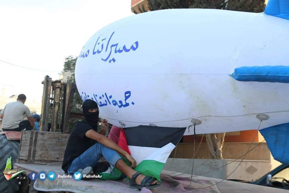 "The Sons of al-Zouari balloon group launches a giant balloon from the central Gaza Strip, threatening the Israeli communities near the border. The Hebrew reads, ""If this is our fate, we won't suffer alone"" (Palinfo Twitter account, October 12, 2018)."