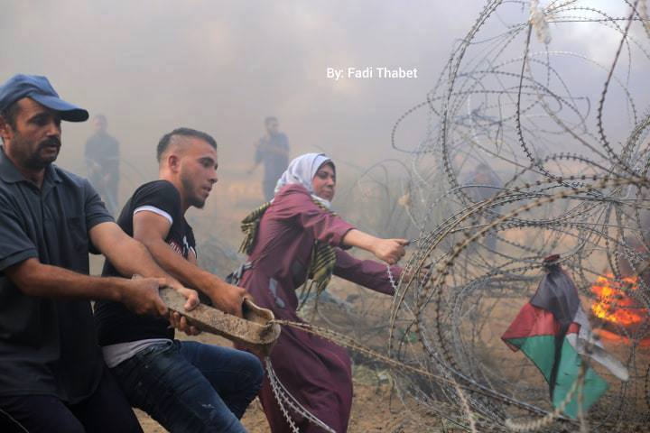 Gazan rioters pull at and yank barbed wire along the security fence in eastern al-Bureij (QudsN Twitter account, October 12, 2018).