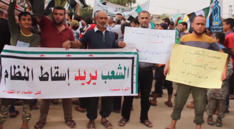 Demonstrators carrying Free Syrian Army flags in the village of Kafararouq, calling for the toppling of the Syrian regime and the removal of Russia and Iran from Syria (Ibaa, October 12, 2018)