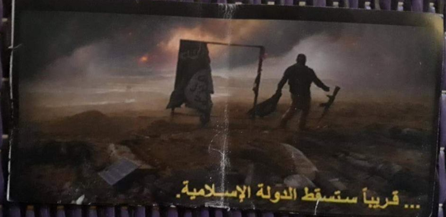 "One of the leaflets dropped by the International Coalition planes, which reads in Arabic, ""The Islamic State will soon fall."" A torn ISIS flag is seen in the background, and an operative laying down his arms."