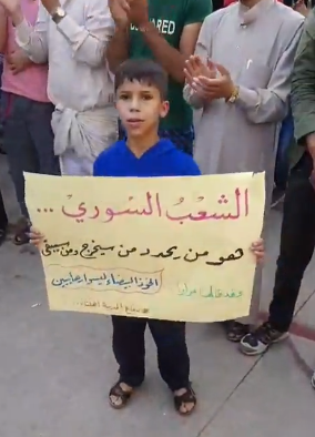 """A boy carrying a sign with the Arabic text: """"The Syrian people […] is the one that will decide who will go and who will stay"""" (Furat Post Facebook page, October 19, 2018)"""