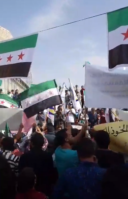 Demonstrators carrying Free Syrian Army flags in the city of Marea, north of Aleppo.