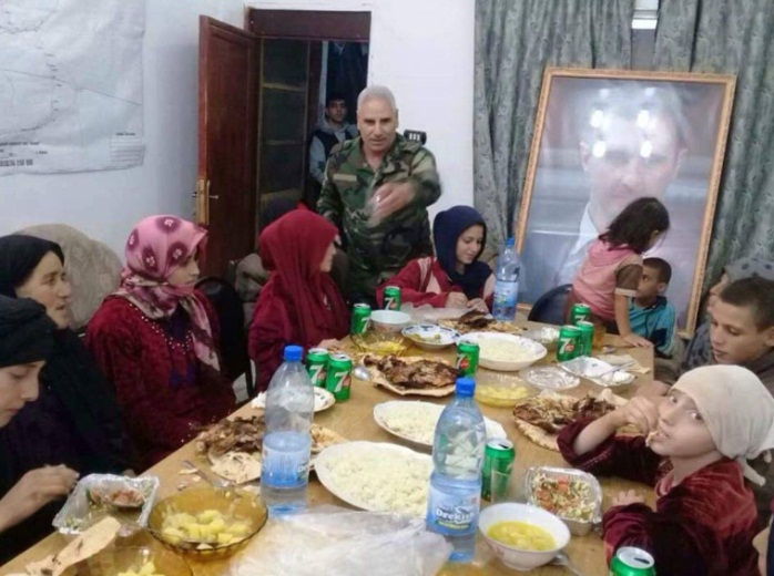 The released Druze abductees together with their children, with a large photo of Syrian President Bashar Assad in the background (Furat Post Facebook page, November 8, 2018).