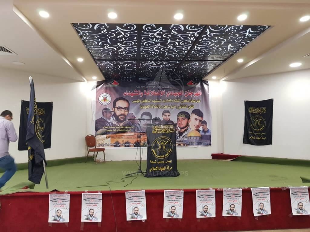 PIJ flags are hung on the stage in al-Bireh. On the back wall are pictures of PIJ founder Fathi Shqaqi, former secretary general Ramadan Abdallah Shalah, and current secretary general Ziyad al-Nakhalah. Next to them are pictures of shaheeds, two of whom have been identified by the ITIC: Muhannad al-Halabi (who carried out a stabbing attack killing two Israelis in the Old City of Jerusalem on October 3, 2015, one of the attacks triggering a wave of popular terrorism); and Muhammad 'Asi, who planned an attack on a bus in Tel Aviv during Operation Pillar of Defense in 2012 (wounding 26 Israelis, one of them critically).[3]