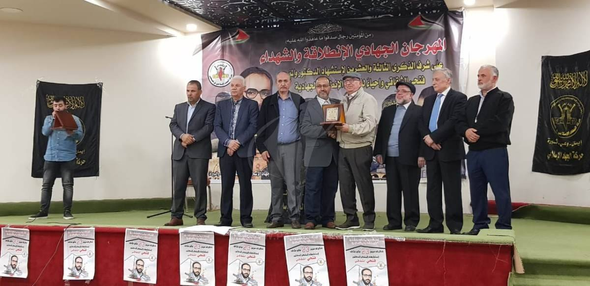 The father of Muhannad al-Halabi (fourth from left) receives a plaque. With him on stage are senior figures from the Palestinian terrorist organizations (Facebook page of the PIJ-affiliated Muhjat al-Quds Association in the Gaza Strip, November 10, 2018).