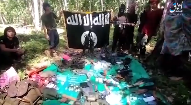ISIS operatives next to the organization's flag, along with weapons and equipment that had been seized (Amaq News Agency, November 19, 2018).