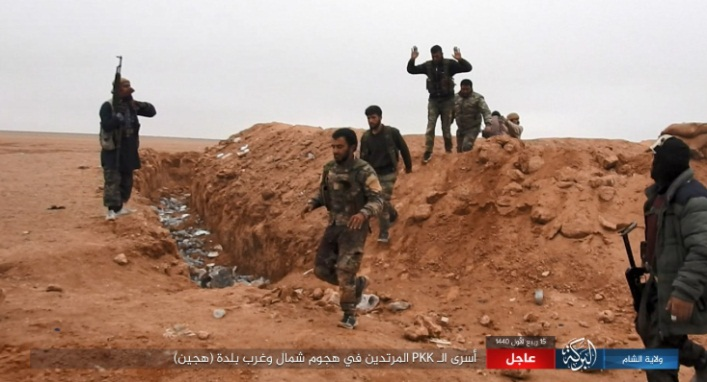 SDF fighters who have manned a position surrounded by an embankment being taken prisoner by ISIS operatives.