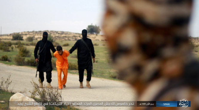 Ayyad al-Breikat wearing an orange jumpsuit, led by two ISIS operatives to the site of his execution (Shumukh, November 26, 2018)