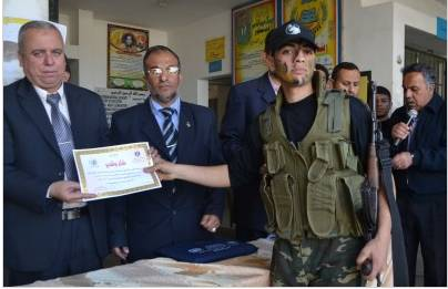 An al-Futuwwa student in the Gamal Abdel Nasser school receives an award from senior figures in the Hamas administration in the Gaza Strip (Dunia al-Watan, April 4, 2013).