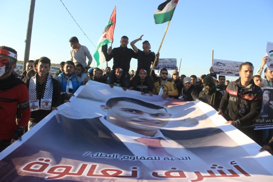"""Demonstrators at the """"return march"""" in eastern Gaza City wave pictures of Ashraf Na'alwa, the terrorist who carried out the shooting attack at the Barkan industrial zone, and of Saleh al-Barghouti, who carried out the shooting attack at the Ofra Junction (Supreme National Authority of the Great Return March Facebook page, December 15, 2018)."""