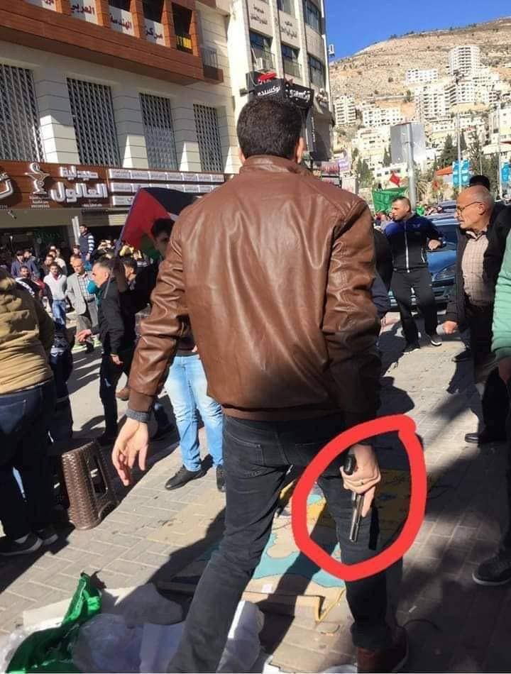Operative in one of the PA's security services wearing civilian clothes and carrying a gun during the dispersal of the parade in Nablus (Twitter account of the Amama website, December 14, 2018).