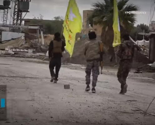 SDF fighters carrying flags walking in the streets of Hajin (YPG Press Office YouTube channel, December 15, 2018)