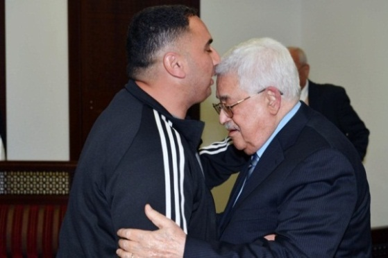 Mahmoud Abbas embraces the murderer, Fatah operative Rajaa'i Hadad, at a ceremony held in his office in Ramallah to celebrate Hadad's release from prison (Wafa, March 14, 2018).