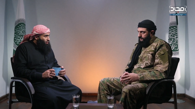 Abu Mohammad al-Julani (right), leader of the HLS (formerly the Al-Nusra Front). In the background are the HLS flags (the HLS-affiliated Amjad Video Production Agency, January 14, 2019)