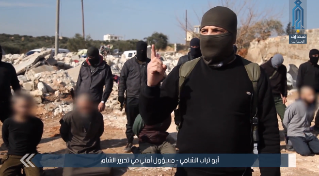 Abu Turab al-Suri, senior security operative of the Headquarters for the Liberation of Al-Sham. ISIS operatives are seen in the background, before being executed. Behind them are the ruins of the command post of the Headquarters for the Liberation of Al-Sham (Ibaa, January 20, 2019).