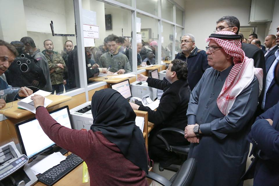 Muhammad al-Amoudi visits a post office in the Gaza Strip to watch the distribution of funds from Qatar.