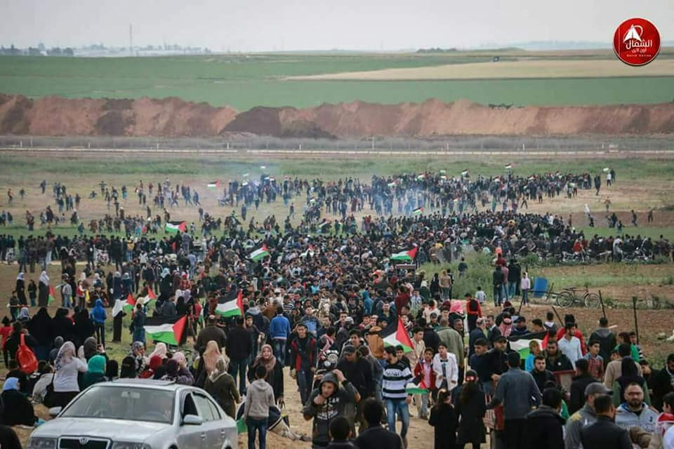 Palestinians gather near the security fence.