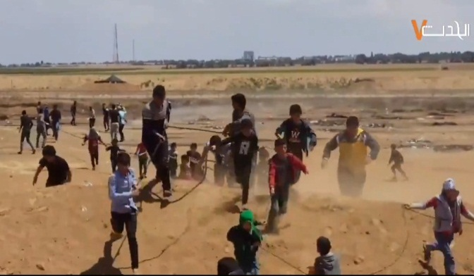 Palestinian children and adolescents approach the border security fence and use a rope to pull at the barbed wire (al-Hadath, April 22, 2018).
