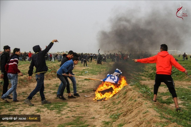 """Return march"" rioters burn tires and an Israeli flag near the security fence in eastern Gaza City (Supreme National Authority Facebook page, February 15, 2019)."