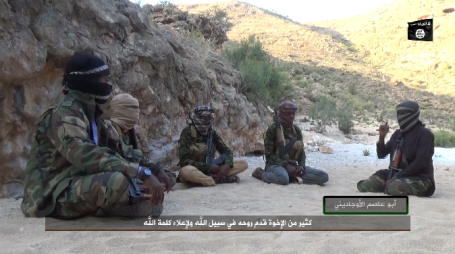 The organization's operatives in Somalia, one of whom is apparently their commander, praising the fatalities of the Caliphate and their devotion to Islam. The ISIS flag appears on the top right.