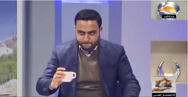 The hidden message to the recruit: the al-Aqsa TV broadcaster puts down his coffee cup to prove the recruit is handled by Hamas (Israel Security Agency website, February 13, 2019).