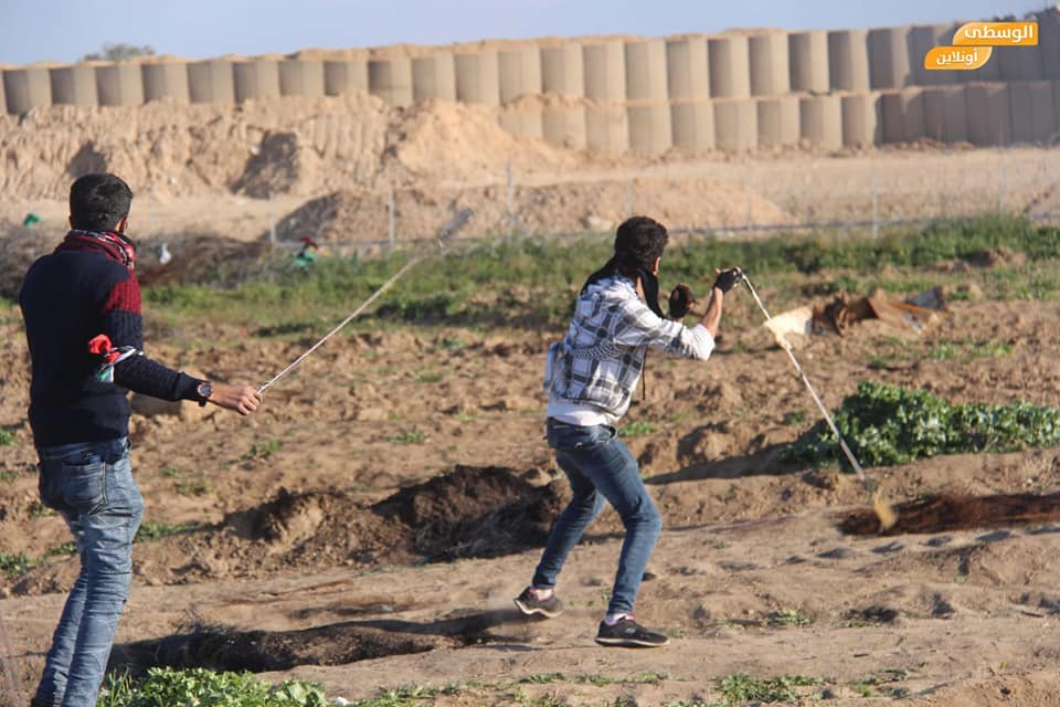"Young Palestinians sling throw near the security fence during the ""return march"" (Supreme National Authority Facebook page, February 23, 2019)."