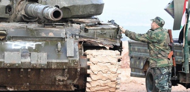 Syrian army soldier near a tank, preparing for the campaign over Idlib (Butulat Al-Jaysh Al-Suri, February 21, 2019).