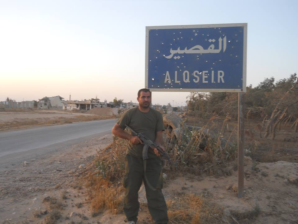 Fatality Qassem Abd al-Raouf Alu (Yasser) near the entrance sign to Al-Qusayr (Facebook).