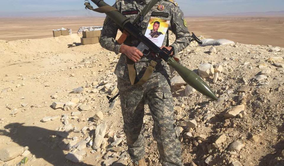 Hezbollah operative holding a photo of fatality Ahmed Nabih al-Hajj (Abu Ali Noh). The operative has a badge with the Hezbollah insignia on his right arm and a badge with the insignia of the Iranian Revolutionary Guards on his left arm.