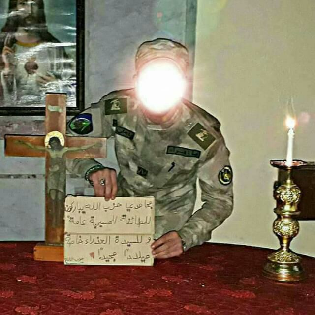 Operative holding a sign wishing the Christian community a Merry Christmas. The operative has a badge with the Hezbollah insignia on his right arm and a badge with the insignia of the Iranian Revolutionary Guards on his left arm.