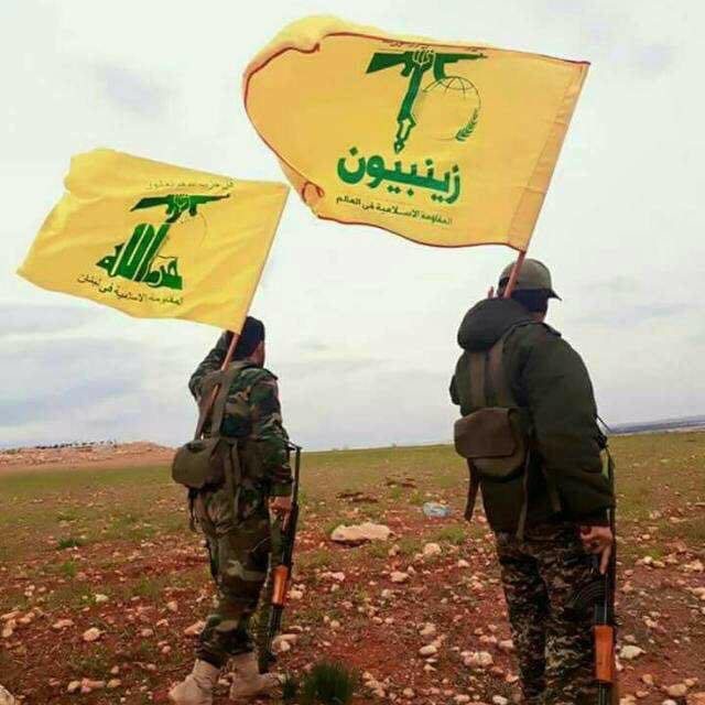 Operative carrying the Hezbollah flag (left) next to an operative (right) carrying a flag of the Zaynabiyoun Brigade. Zaynabiyoun is a Shiite militia fighting in Syria, established by Iran on the basis of fighters from Pakistan.