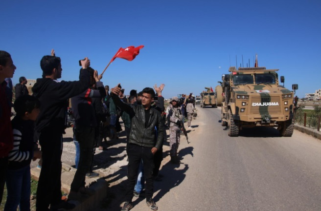 Convoy of Turkish patrol vehicles welcomed by local residents waving Turkish flags.
