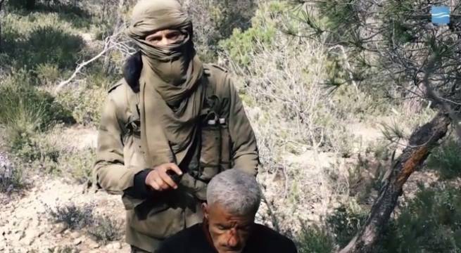 "ISIS operative holding a knife. An ""agent"" of the Tunisian security service is kneeling in front of him before being executed (Shabakat Shumukh, March 16, 2019)."
