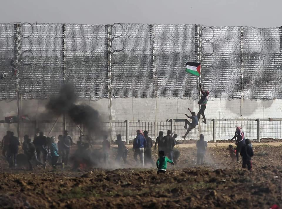 Rioters climb the border fence east of Gaza City (Supreme National Authority Facebook page, March 22, 2019).